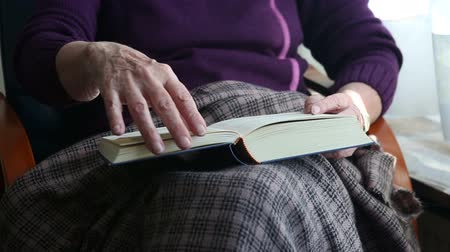 бабушка : older woman sitting by window and reading a book Стоковые видеозаписи