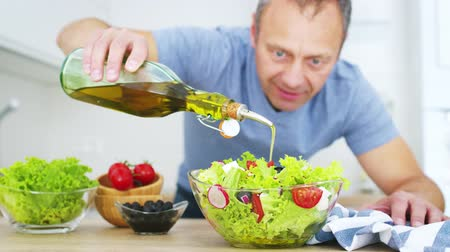 olive oil pour : Man cook pouring olive oil into the fresh vegetable salad in his kitchen. Slow motion video shot on Black Magic Cinema camera 6K on RAW format. Stock Footage