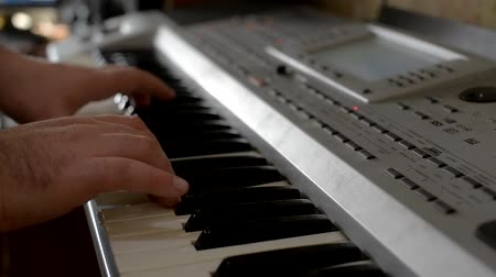 piano parts : Wire the musical equipment. Setting up electronic drums. A man plays the melody on the keyboard. Smooth movement of the sliders. Working with crossfade. The man plays on a red electric guitar. Drummer playing on electronic drums.