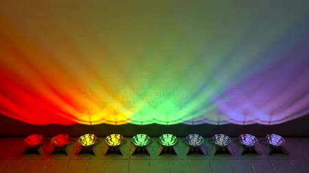 épült : Spotlights are built on the floor in a row and illuminate the wall. Smooth change of colored light. Stock mozgókép