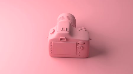 pop art background : Cool professional camera revolves around its axis. All painted in one fashionable pink and pastel color. Illustration in Minimal style. 3d rendering.