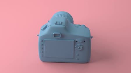 professional photography : Cool professional blue camera revolves around its axis. Background painted in fashionable pink and pastel color. Illustration in Minimal style. 3d rendering. Stock Footage