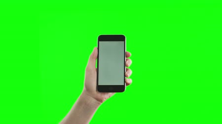 мобильный телефон : Female hand holding the new smartphone on green screen. Extremely high quality. 4K resolution. Shot on Red camera. The newest phone model. No need in green or blue screen into the phone. You can track it easily putting the trackers on the screen corners.