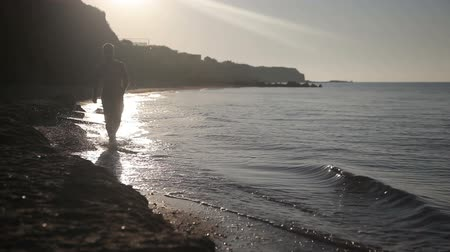 A man walks along the seashore