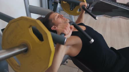 Young man bench pressing weights at a gym
