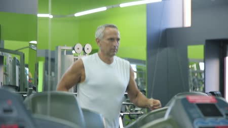 Old man runs on a treadmill