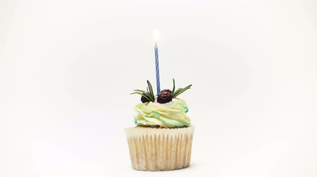 kihalt : birthday cupcake with one burning candles over white background
