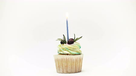 blussen : birthday cupcake with one burning candles over white background