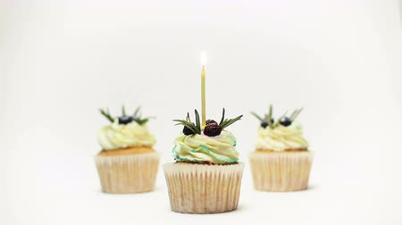 kihalt : birthday three cupcake with one burning candles over white background