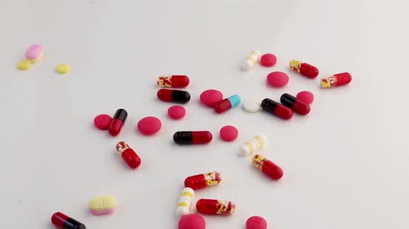 the inflammation : Medicine Capsules Dropping on white background