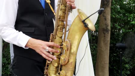 джаз : Saxophonist in black suit play jazz on golden saxophone with microphone. Music. Live performance