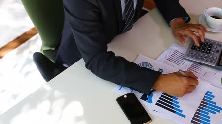businessman in suit working with paper graph chart analysis