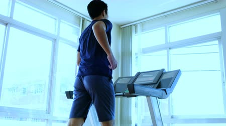 Close-up footage of asian man male running on treadmill in sport gym. Shot on in 4K (UHD).