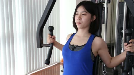 cute Young Asian woman in blue color sport wear workout exercising on the fly machine in the fitness center gym