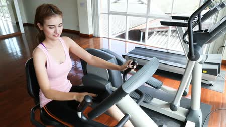 Attractive caucasian woman is workout on an exercise bike. woman  in the fitness center. Sports caucasian woman on a stationary bike with happiness