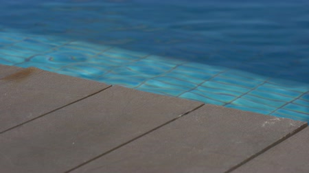 vacation holiday moment with wooden deck and blue mosaic swimming pool
