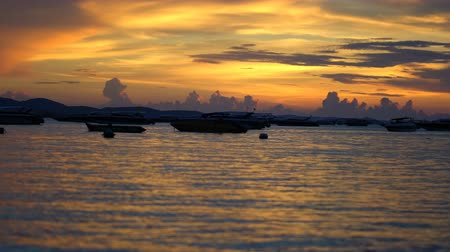 BEAUTIFUL GOLDEN CLOUD SUNSET WITH FISHERMAN BOAT ON THE OCEAN IN PATAYA THAILAND