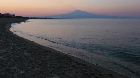 augusta : Beautiful sunset twilight on Agnone Bagni sea beach with smoky Etna volcano in far (Siracusa, Sicily, Italy). Unrecognizable people pair have fun bathing and swiming in far.