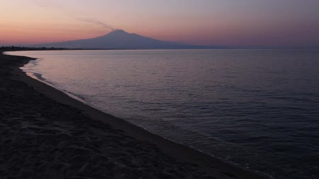 augusta : Beautiful sunset twilight on Agnone Bagni sea beach with smoky Etna volcano in far (Siracusa, Sicily, Italy)