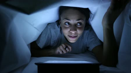 cover : Furtive Woman Using Digital Tablet under Bed Sheets Stock Footage