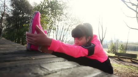 atletismo : Young woman doing stretching exercises at park