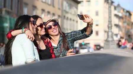 kentsel : Three happy girls taking a selfie in the city. This is a mixed race group one girl is half asian and one is middle eastern. Lifestyle friendship and urban life concepts. Stok Video
