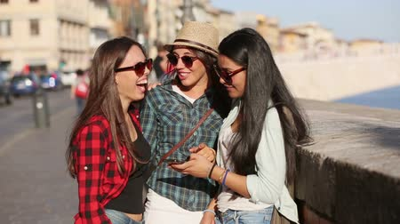 покупка товаров : Three young women with smart phone in the city talking and smiling. This is a mixed race group one girl is half asian and one is middle eastern. Lifestyle friendship and urban life concepts.