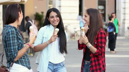chatting : Three happy women eating ice cream in the city talking and smiling. This is a mixed race group one girl is half asian and one is middle eastern. Lifestyle friendship and urban life concepts. Stock Footage