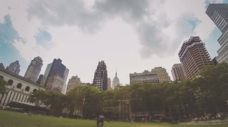 parky : New York, Time-lapse view of Bryan Park with clouds passing over the mid-town Manhattan skyscrapers. Blurred foreground to avoid people being recognizable. Dostupné videozáznamy