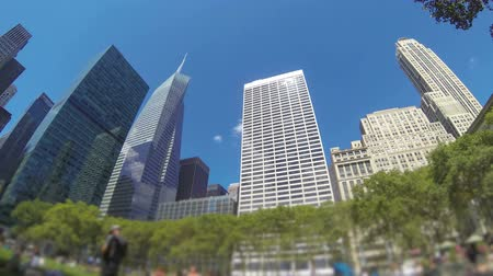 önlemek : New York, time-lapse view of Bryant Park, with clouds passing over the midtwon Manhattan skyscrapers. Blurred foreground to avoid people being recognizable.