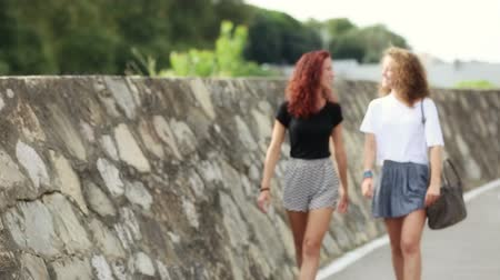 parecer : Two girls walking on the footpath, they are friends and seem to be happy. Summer time, early morning. They walk from out of focus to focus. Lifestyle and friendship concepts.