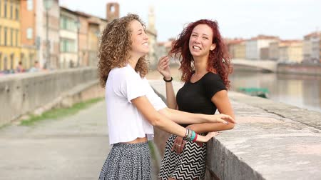 kıvırcık saçlar : Two girls talking and laughing together outdoor. They are standing against a small wall with a river and an Italian cityscape on background. Friendship and lifestyle concepts. Stok Video