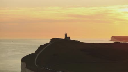 cliff : Panoramic view of Seven Sisters cliffs with lighthouse and sea on background at sunset. Video taken from Beachy Head, on Eastbourne side. Pan view with movement.