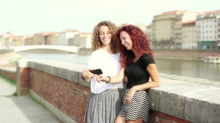 гей : Two happy girls looking at smart phone with Italian city on background. They are leaning to a small wall and there is a river behind them. Technology and lifestyle concepts. Стоковые видеозаписи