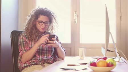 kudrnatý : Young woman working at home or in a small office, vintage hipster clothing, curly hair. She seems to be stressed or thoughtful, There is a cup of tea or coffee on the desk with some technological devices.