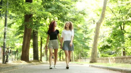leszbikus : Two beautiful girls walking holding hands at park. They are happy and smiling each other. They could be friends or a couple, lifestyle and friendship concepts. They walk in from out of focus zone.
