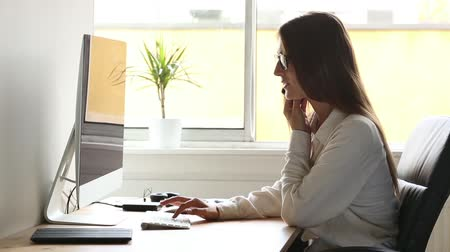 бухгалтер : Young woman at work, answering and talking on the phone. Home office or small company situation with real people. Стоковые видеозаписи