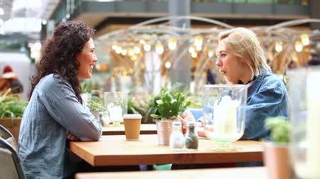 leszbikus : Two women having a coffee together and enjoying life in London. They are on their mid twenties, one blonde and one brunette, looking each other and sitting at the table in a cafe. Stock mozgókép