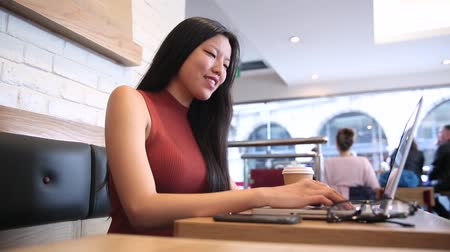 studenci : Woman typing on computer keyboard in a cafe. Chinese woman looking at monitor and typing