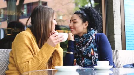 leszbikus : Lesbian couple at a cafe. Two young women are having a coffee together, talking, cuddling and give each other a kiss. Candid situation with real people. Homosexuality and lifestyle concepts.