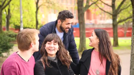 дружба : Group of friends having fun at park in Berlin. Mixed race group with caucasian, middle eastern and nordic persons, sitting on a bench and talking. Happiness and friendship concepts.