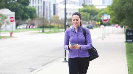 tek başına : Young woman walking on the pavement and typing on the phone. Beautiful woman wearing training suit and holding a bag, going to gym. Lifestyle and sport concepts