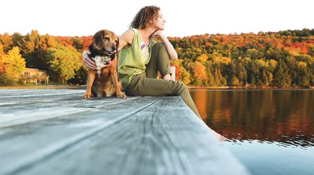 abraços : Woman and dog relaxing on the dock. Autumn colors, unstaged situation with candid model and her dog. Relaxation and friendship concepts. Vídeos