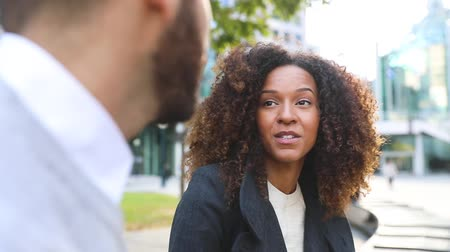 multirracial : Business woman and man talking, slow motion. Business people meeting on a break, chatting and laughing. Mixed race beautiful couple outdoors in the city. Business and lifestyle concepts Vídeos