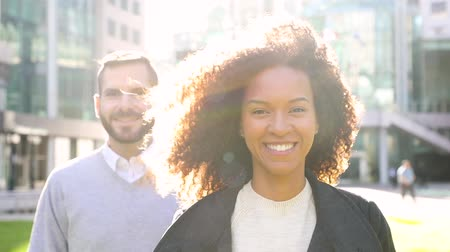 смешанной расы человек : Portrait of a business woman with a man on background, slow motion. Smiling mixed race woman with curly hair looking at camera. Teamwork and business concepts Стоковые видеозаписи
