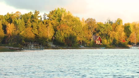 à beira do lago : Lakeside view at sunset with trees, a small house and a boat. Nature and travel concepts in the remote area of ??Canada