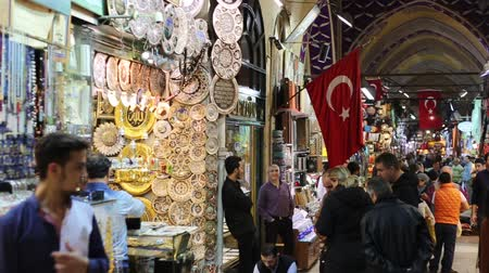 romênia : ISTANBUL, TURKEY - OCTOBER 27, 2014: People at Grand Bazaar, the main market of the city, with Turkish flags in front of some shops. There are people with different ethnicities and wearing dirrent style of clothes