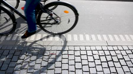 kodaň : People cycling in Copenhagen, focus on bicycle shadows. Side view of a bicycle lane in the Danish capital, with many persons commuting by bike.