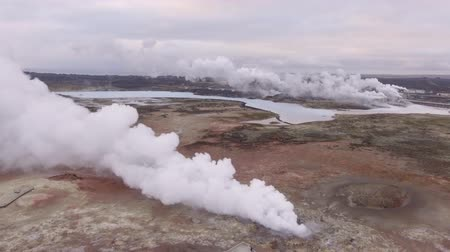 geyser iceland : Gunnuhver hot springs in Iceland. Steam coming out from the earth and flowing over the ground. Geothermal power plants on background. Nature and industry concepts in Iceland