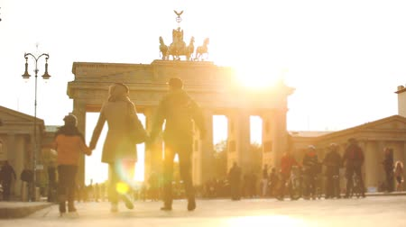 tor : Berlin Brandenburg gate at sunset with backlight. Blurred silhouette of people walking in Paris Square with the famous building on background. German name is Brandenburger Tor